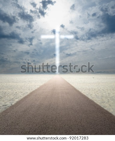 Road in sand leading to glowing cross - stock photo