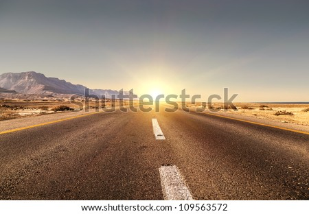Road in the desert and sunset - stock photo