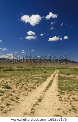 Road in the desert receding into the cloud - stock photo