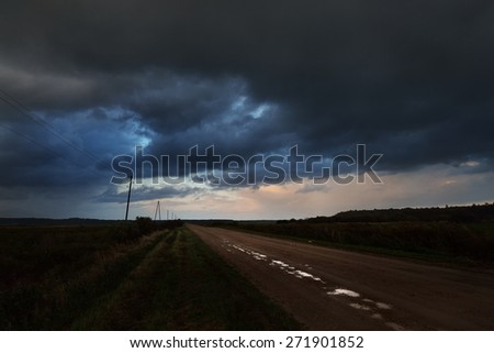 Road in the field and the dark dramatic rain clouds. Autumn in Latvia.