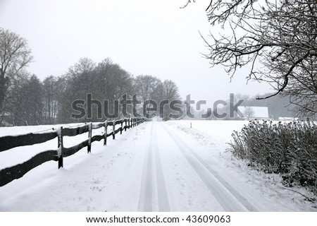 road in winter during snowfall - stock photo