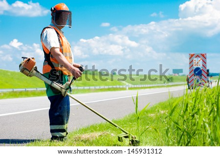 Road landscaper cutting grass along the highway using string lawn trimmer - stock photo