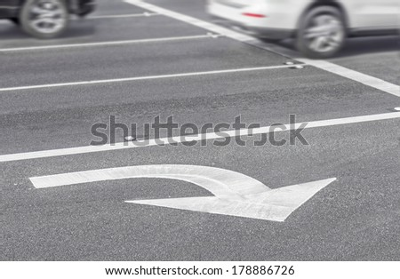 Road lane marking right turn arrow and car blurred motion. White painted lines on grey asphalt. Busy urban traffic concept. Horizontal photo. - stock photo