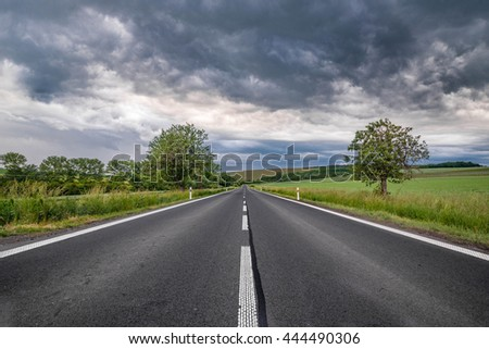 road leading in the middle of the picture with heavy clouds in the sky - stock photo