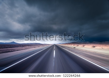 Road leading into a desert storm - stock photo