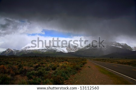 Road leading into a High Mountain Storm - stock photo