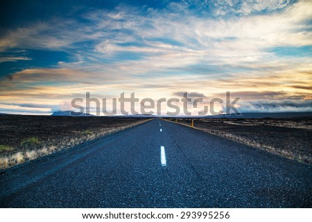 Road leading into the distance under a dramatic sky - stock photo