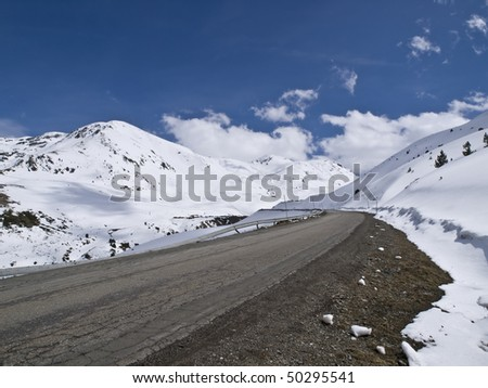 Road leading to a beautiful snowy landscape - stock photo