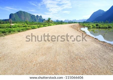 road leading to horizon with dramatic sky - stock photo