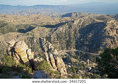 Road leading up to Mt. Lemon and Santa Catalina Mountains with Tucson in background. - stock photo
