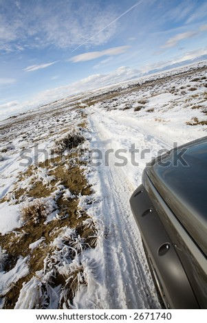 road less traveled - suv exploring a remote road in wyoming covered with snow and frost - stock photo