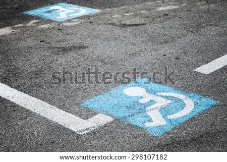 Road marking of place for disabled persons on urban parking lot - stock photo