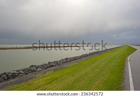 Road on a dike along a lake in autumn - stock photo