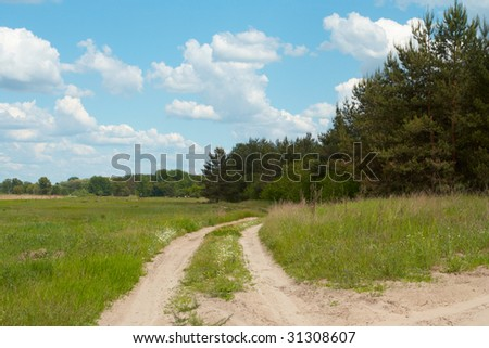 road on a meadow and blue cloudy sky