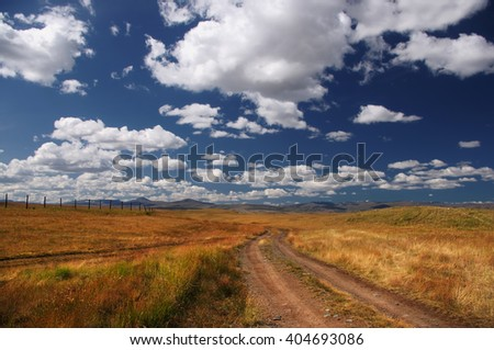 Road on a wild mountain plateau with the orange grass at the background of the hills under a blue sky with white clouds, Plateau Ukok, Altai mountains, Siberia, Russia - stock photo