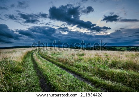 Road on the meadow with the dark clouds on the sky - stock photo