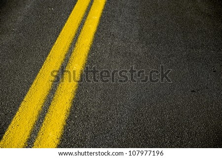 Road Pavement Backdrop - Black Road Pavement with Yellow Double Line. Travel and Transportation Background Theme.