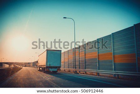 Road perspective. Photo from front car glass at sunset light with flares. Traveling mood concept.