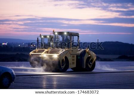 Road repair, vibration rollers at asphalt pavement works - stock photo