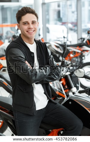 Road rider. Vertical portrait of a hot handsome man smiling to the camera cheerfully with his arms crossed sitting on his new motorbike