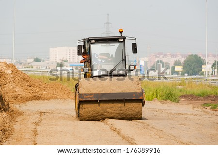 Road roller compressing sand to highway construction