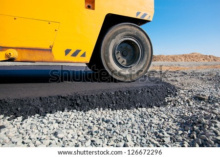 Road roller laying fresh asphalt pavement on top of the gravel base during road construction - stock photo