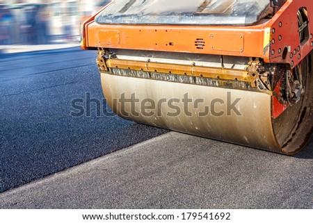 Road roller repairing asphalt pavement - stock photo