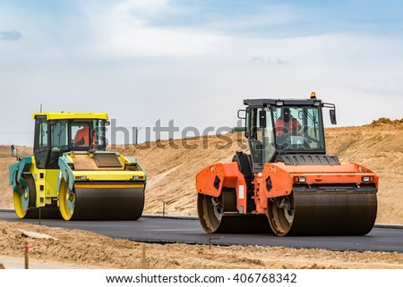 Road rollers building the new asphalt road - stock photo