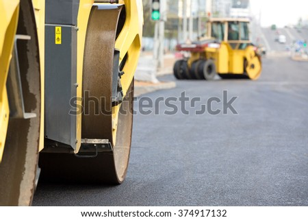 Road rollers vibration machines compacting fresh asphalt during construction roadworks - stock photo