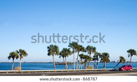 Road running alongside blue water and green palm trees. Red van motion blurred. - stock photo