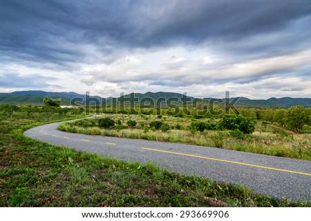 Road running through green hills in rainy season.Thailand. - stock photo