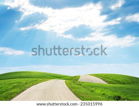 Road running through green hills towards horison - stock photo