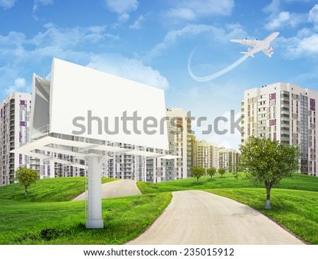Road running through green hills with some trees, towards high-rise buildings with jet lowering above. Blank billboard with lighting on foreground. - stock photo