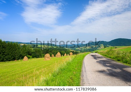 Road rural haystack landscape view clouds sky countryside summer, Beskid Niski Mountains, Poland - stock photo