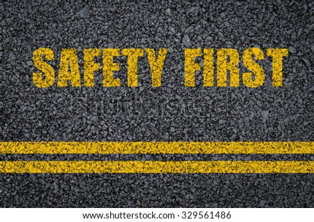 Road safety concept: Yellow safety first on asphalt with center lines