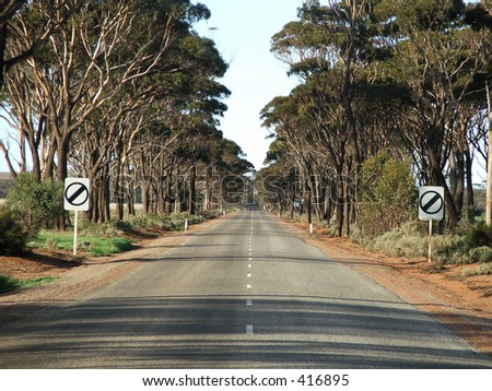 Road showing end of speed limit signs - stock photo