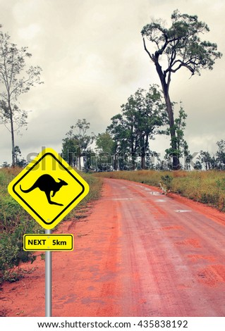 road sign and kangaroo in the outback road - stock photo