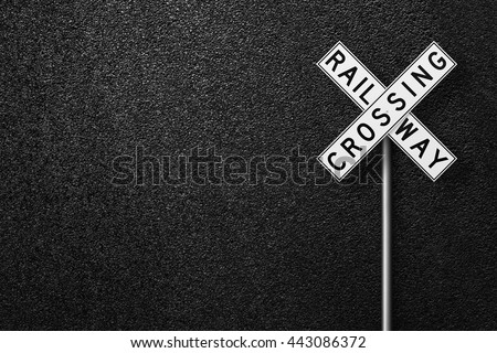 Road sign. Behind the sign one can see a smooth asphalt road. RAIL WAY CROSSING. The texture of the tarmac, top view. - stock photo