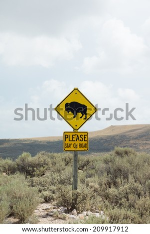 """Road sign """"Bison"""" and """"Please stay on the road."""" Warns that the road may go wild animals and can be dangerous - stock photo"""