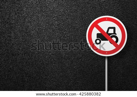 Road sign circular shape with a picture of the tractor. Behind the signs one can see a smooth asphalt road. The texture of the tarmac, top view. - stock photo