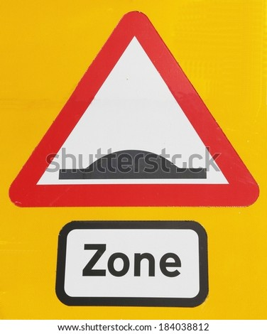 Road sign depicting a speed hump zone ahead on a yellow background. - stock photo