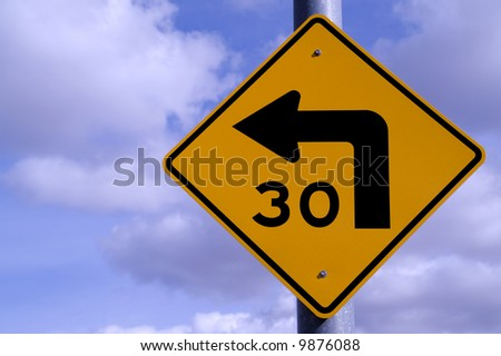 Road sign for 30 mph curve ahead against blue sky with clouds