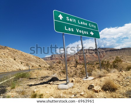 Road sign in desert pointing towards Salt Lake City and Las Vegas.
