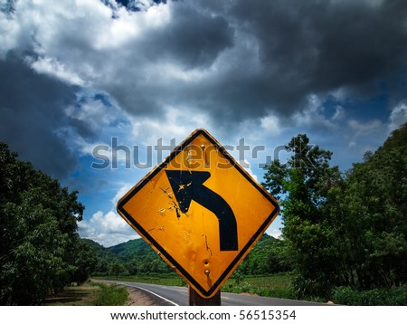 Road sign in left curve - stock photo