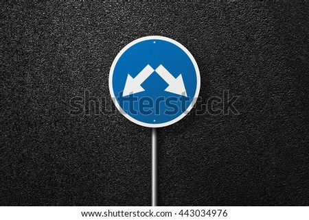 Road sign of the circular shape with pointer on a background of asphalt. Detour. The texture of the tarmac, top view. - stock photo