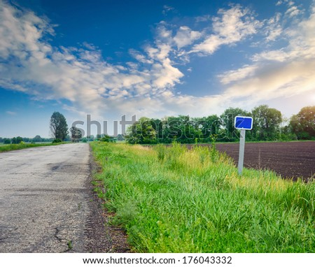 road sign on the grass beside the road in a landscape - stock photo