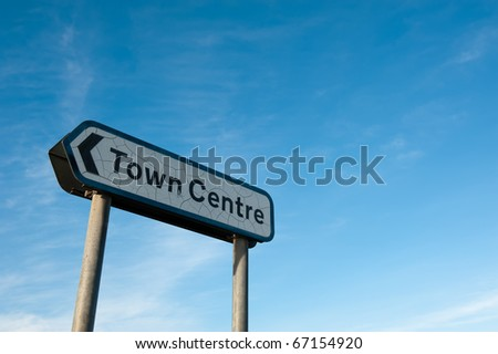 Road sign pointing to Town Centre with blue sky and copy space