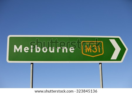 Road sign to Melbourne, Australia pointing to right side of frame, nice clear blue sky behind. Lots of copy space. - stock photo