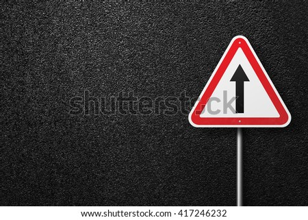 Road sign triangular shape with pointer. Behind the signs one can see a smooth asphalt road. The texture of the tarmac, top view. - stock photo