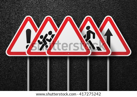 Road signs of the triangular shape are placed in a row. Behind the signs one can see a smooth asphalt road. The texture of the tarmac, top view. - stock photo
